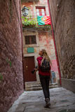 Girl with blonde dreadlocks with camera explores old portugese town. Stock Image