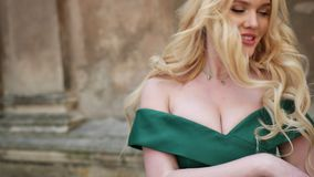 Miss, blonde, in green dress with bare shoulders, with crown, posing for camera