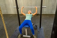 The girl blonde in a green T-shirt and blue pants first doing a stock image