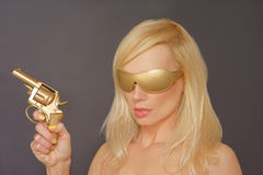 Girl With Blonde Hair Holding a Gun Royalty Free Stock Photo