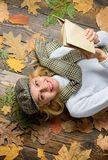 Girl blonde lay wooden background with leaves. She likes detective genre. Woman lady in checkered hat and scarf read. Book. Girl in vintage outfit enjoy royalty free stock images