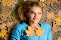 Girl blonde lay on wooden background with orange leaves top view. Fall atmosphere attributes. Fall and autumn season. Concept. Woman pretty lady enjoy cozy royalty free stock images