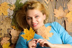 Girl blonde lay on wooden background with orange leaves top view. Fall and autumn season concept. Woman pretty lady. Enjoy cozy season hold autumn dry leaves royalty free stock photos