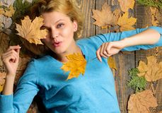 Girl blonde lay on wooden background with orange leaves top view. Fall and autumn season concept. Woman pretty lady. Enjoy season hold autumn dry leaves. Fall stock photos