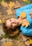 Girl blonde lay on wooden background with orange leaves top view. Woman pretty lady enjoy cozy season hold autumn dry. Leaves. Fall atmosphere attributes. Fall stock photos