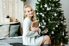 Girl the blonde in a light cozy sweater opens Christmas gifts royalty free stock images