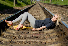 Girl blonde lying on the rails Stock Photo
