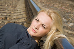 Girl blonde put her head on the rails Royalty Free Stock Photos