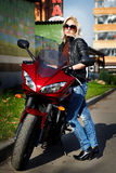 The girl blonde about a red motorcycle Royalty Free Stock Images