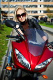 The girl blonde sg on red motorcycle Royalty Free Stock Images
