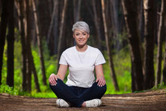 Girl blonde with short hair, resting sitting in the fir forest. Portrait of a young, beautiful, smiling girl, Stock Images