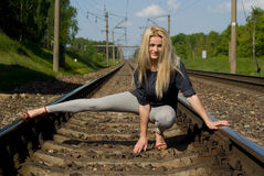 Girl blonde sitting on the rails Royalty Free Stock Image