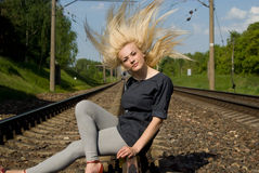Girl blonde sitting on the rails Royalty Free Stock Photography