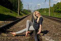 Girl blonde sitting on the rails Stock Photography