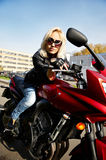 The girl blonde sitting on red motorcycle Stock Photo
