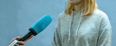 The girl the blonde in a sports light sweater gives interviews. Abstract image of a teenager. Female correspondent hand is holding royalty free stock photography