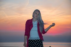 Girl blonde and sunset sky stock photography