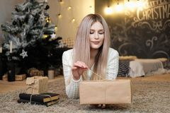 The blonde girl lies at home on the carpet and holds a gift box in her hands. Christmas garlands and home comfort. stock photography