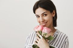 Girl blooming from love like this flowers. Portrait of sensual attractive girlfriend, smiling broadly while holding royalty free stock image
