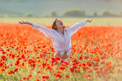 Girl at blooming poppy field Stock Photos