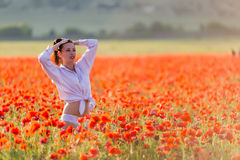 Girl at blooming poppy field Royalty Free Stock Photos