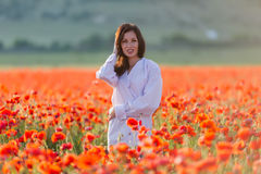 Girl at blooming poppy field Royalty Free Stock Photo