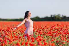 Girl at blooming poppy field Stock Image