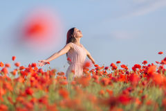 Girl at blooming poppy field Stock Photography