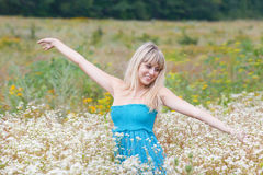 The girl in a blossoming field. The girl smiles among a blossoming field Stock Photography