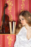 Girl in blouse in room near violin Stock Photo