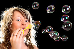 Girl blow bubbles. Girl blow soap bubbles around her Stock Photography