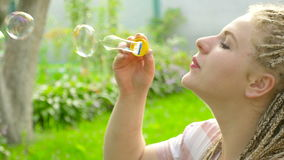 The girl blow bubbles outdoors. 4K stock footage