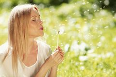Girl blow on dandelion. Happy blond Girl blow on dandelion in spring park stock images