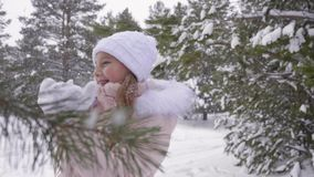 Girl blow snow from palms throw snow up and turn around in forest winter snowfall, show thumbs up. In white knitted white warm mittens, Joyful smile at stock footage