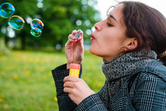 Girl blow soap bubble. Against a background grass Stock Image