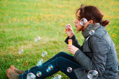 Girl blow soap bubble. Against a background grass Stock Photos