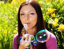 Girl blow soap bubble against a background grass Royalty Free Stock Photography