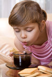 Girl blow to hot tea Royalty Free Stock Images