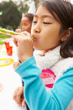 Girl With Blower At Outdoor Birthday Party Stock Photo
