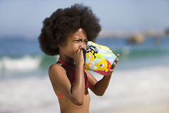 Girl (8-10) blowing air into inflatable armband, standing on sandy beach, side view Stock Photo