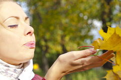 Girl blowing away a leaf Stock Image