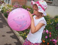 Girl blowing a balloon Royalty Free Stock Images