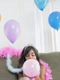 Girl Blowing Balloon On Sofa Stock Photo