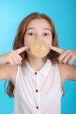 Girl blowing a big bubble gum bubble Stock Photo