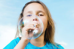 Girl is blowing big soap bubble Royalty Free Stock Image