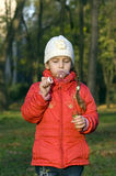 Girl blowing a bubble. Little girl in a red jacket inflates bubble Royalty Free Stock Photos