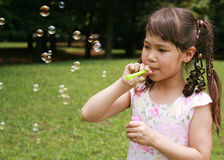 Girl blowing bubble. In the park Stock Photo