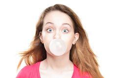 Girl blowing bubble from chewing gum. Beautiful and shocked or surprised young student girl blowing bubble from chewing gum. Looking into the camera. Isolated on royalty free stock photo