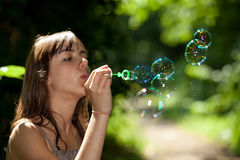 Girl blowing bubble soap Stock Photos