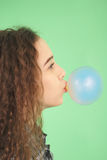 Girl blowing a bubblegum bubble. Isolated on green Stock Photos